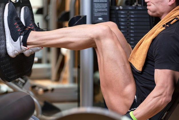 Handsome strong man performed leg press workout in the gym.
