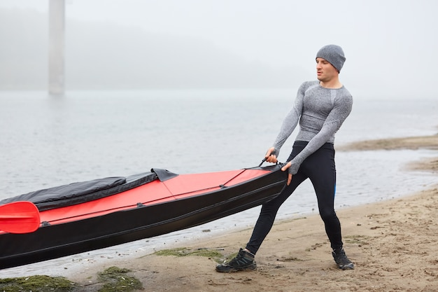 Красивый сильный мужчина вытаскивает лодку из воды, одетый в спортивную одежду, пудинг на озере