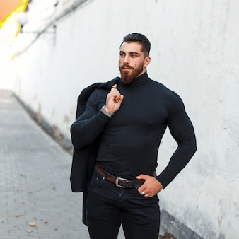 Handsome strong man with a beard in black stylish clothes posing on the street
