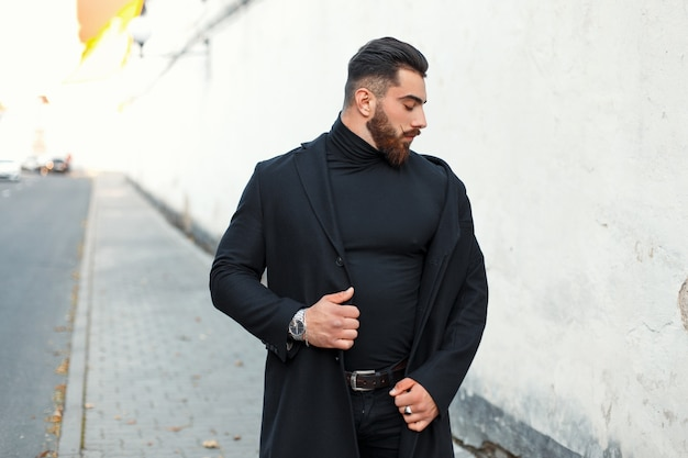 Handsome strong man with a beard in a black trendy coat walks on the street