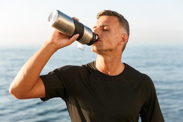 ビーチで飲んでハンサムな強い成熟したスポーツマン。