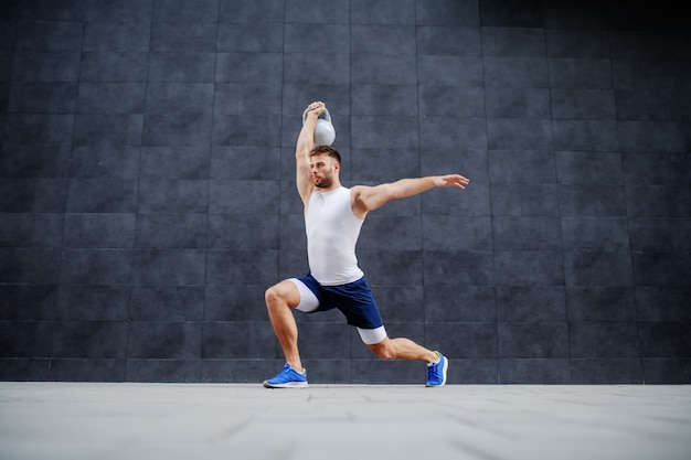 Handsome strong muscular caucasian man in shorts and t-shirt doing lunges and holding kettle bell. in background is gray wall.