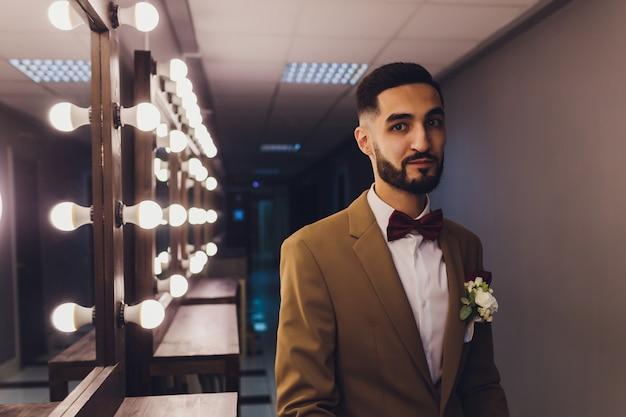 Handsome strong stylish bearded groom posing near mirror.