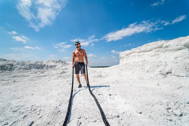 ハンサムなストロングマンが採石場を歩きます。白い風景。 。採石場での写真撮影。アウトドアスポーツのコンセプト。ロープでのトレーニング。