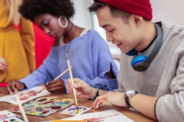 ハンサムな学生。絵筆を持っている赤い帽子をかぶっているハンサムな晴れやかな黒髪の芸術学生