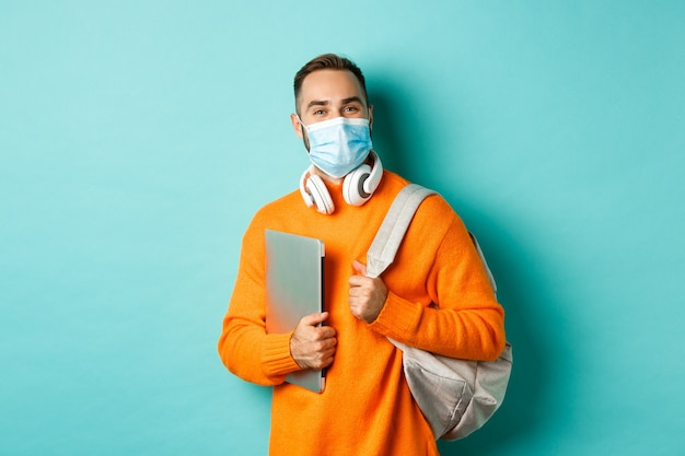 フェイスマスク、バックパックとラップトップを持って、仕事に行く、水色の背景の上に立っているハンサムな学生。