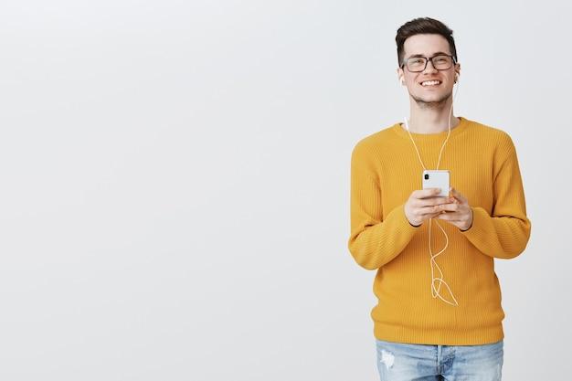 Красивый студент в очках, слушающий muisc в наушниках и обменивающийся сообщениями через смартфон