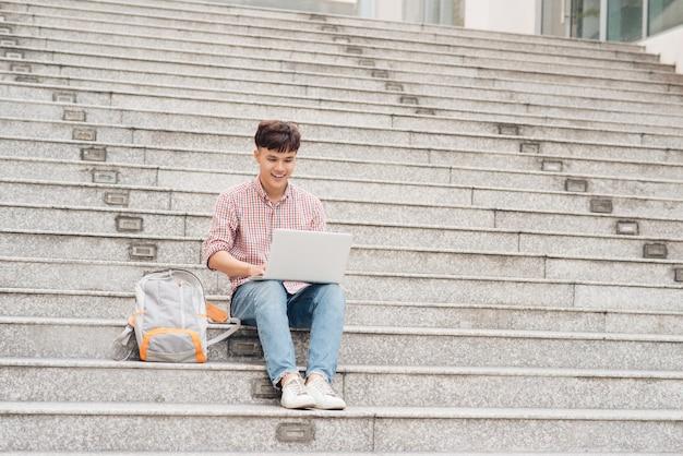 대학 계단에 앉아 노트북 작업을 하는 셔츠를 입은 잘생긴 학생