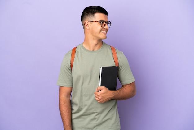 Красивый студент человек на изолированном фоне смотрит сторону