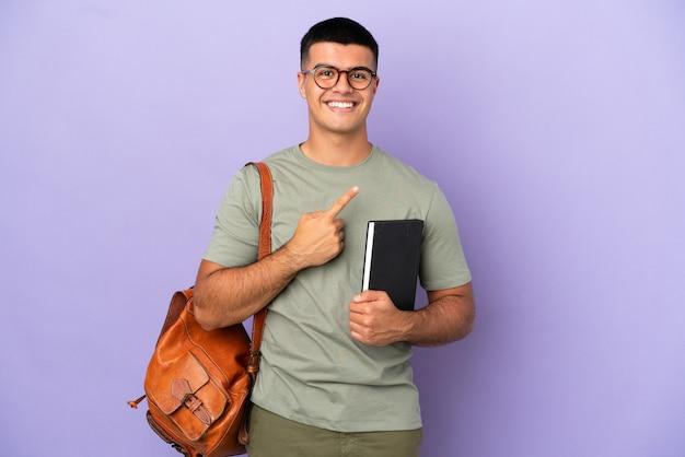 Красивый студент человек на изолированном фоне, указывая в сторону, чтобы представить продукт