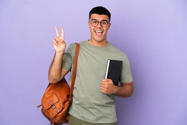 Красивый студент человек на изолированном фоне улыбается и показывает знак победы