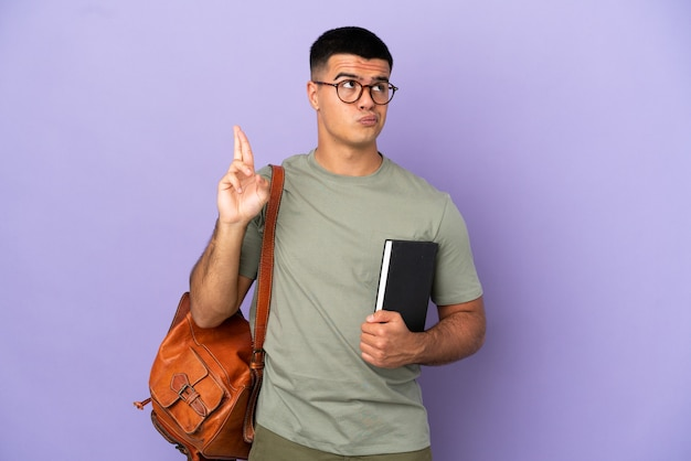 Красивый студент-мужчина на изолированном фоне со скрещенными пальцами и желанием всего наилучшего