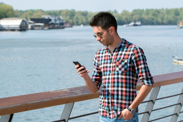 Handsome student uses a mobile phone beside the river.