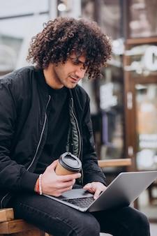 Красивый студент с вьющимися волосами, используя ноутбук