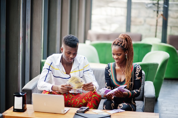 Handsome stylish african american couple sitting at office together with laptop and money.