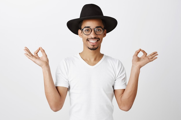 Handsome stylish african american guy in hipster hat and glasses meditating, practice yoga