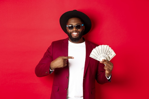 Modello maschio afroamericano bello ed elegante che mostra soldi e sorridente, indossando occhiali da sole e cappello fantasia, in piedi su sfondo rosso.