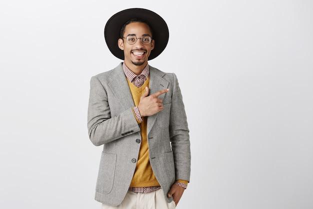 Bello elegante uomo afro-americano che punta il dito a destra al banner promozionale