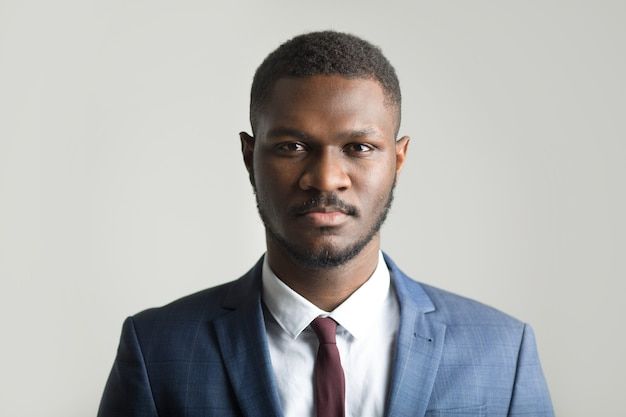 Handsome stylish african man in a suit on a gray background