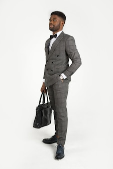 Handsome stylish african man in suit with bag in hand on white background