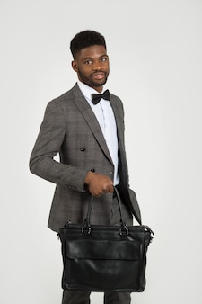 Handsome stylish african man in suit with bag in hand on white wall