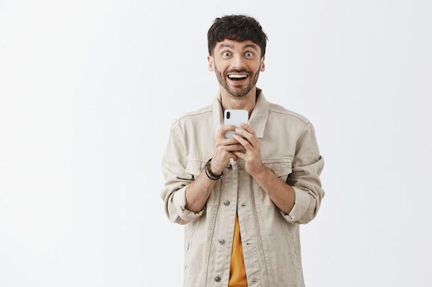Красивый стильный бородатый парень позирует у белой стены