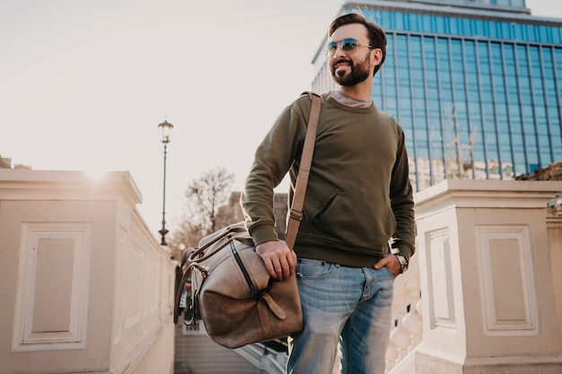 Handsome stylish bearded man walking in city street with leather travel bag wearing sweatshirt and sunglasses, urban style trend, sunny day, confident and smiling