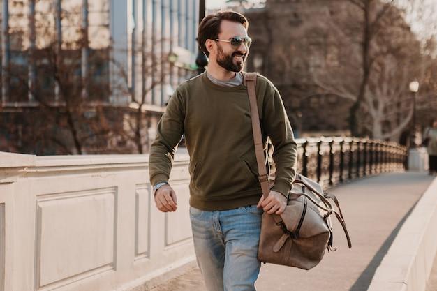 Красивый стильный бородатый мужчина идет по городской улице с кожаной дорожной сумкой в толстовке и солнцезащитных очках, тренд городского стиля, солнечный день, уверен в себе и улыбается