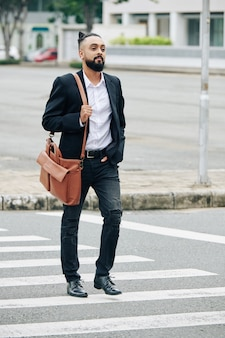道路を横断する革のバッグを持つハンサムなスタイリッシュなひげを生やした男