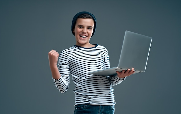 그의 손에 노트북 스트라이프 스웨터와 모자에 잘 생긴 세련 된 소년 네 회색에 고립 된 제스처를 보여줍니다.