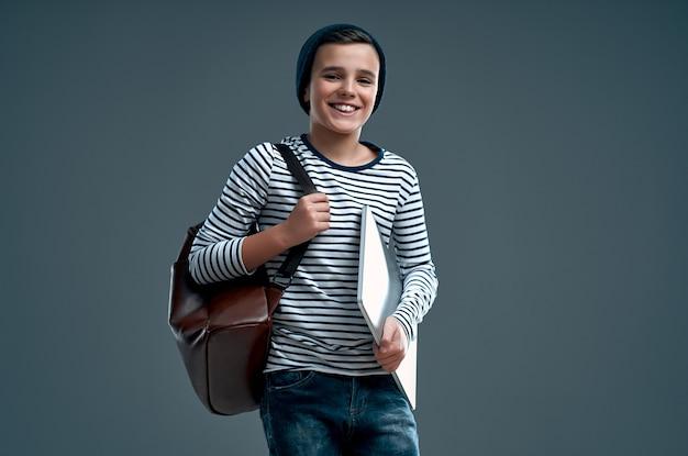 Красивый стильный мальчик в полосатом свитере с кожаным рюкзаком и шляпе с ноутбуком в руке, изолированной на сером.