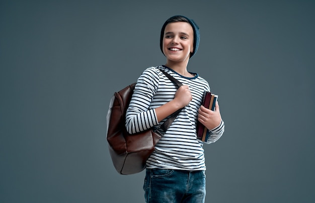 Красивый стильный мальчик в полосатом свитере с кожаным рюкзаком и шляпе с книгами в руке, изолированной на сером фоне.