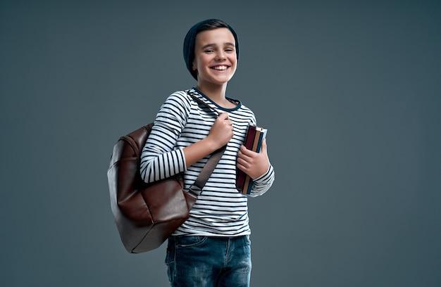 Красивый стильный мальчик в полосатом свитере с кожаным рюкзаком и шляпе с книгами в руке, изолированной на сером.