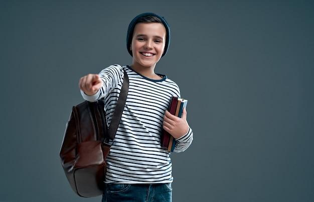 Красивый стильный мальчик в полосатом свитере с кожаным рюкзаком и шляпе с книгами в руке показывает пальцем на камеру, изолированную на сером.