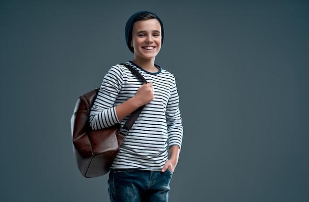 Красивый стильный мальчик в полосатом свитере с кожаным рюкзаком и шляпой, изолированной на сером.