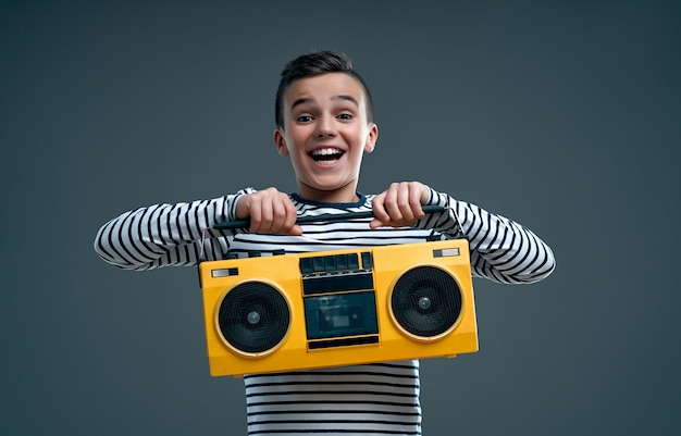Handsome stylish boy in a striped sweater with a yellow retro tape recorder isolated on a gray.