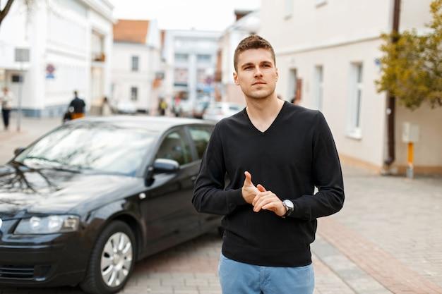 검은 차 근처에 검은 티셔츠와 파란색 바지에 잘 생긴 세련된 사업가