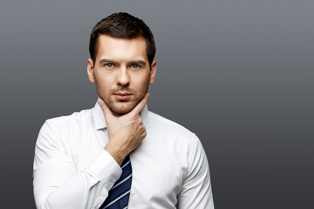 灰色の背景にハンサムなスタイリッシュなビジネスマン