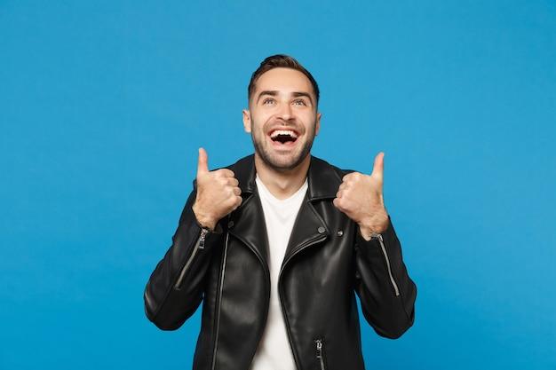 ハンサムなスタイリッシュな楽しい若いひげを生やした男は、青い壁の背景のスタジオの肖像画に分離された黒革のジャケット白いtシャツを探しています。人々の誠実な感情のライフスタイルの概念。コピースペースをモックアップします。