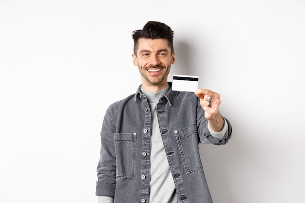 Handsome stylish guy showing plastic credit card and smiling, satisfied client standing on white background.