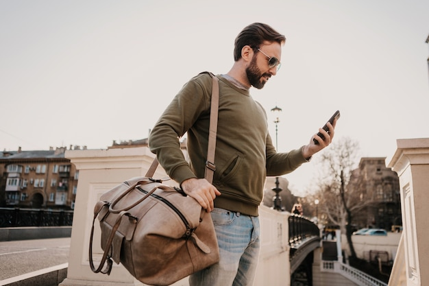 Handsome stylish hipster man walking in city street with leather bag using phone navigation application, travel wearing sweatshirt and sunglasses, urban style trend