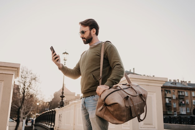 Handsome stylish hipster man walking in city street with leather bag using phone, travel wearing sweatshirt and sunglasses, urban style trend, sunny day
