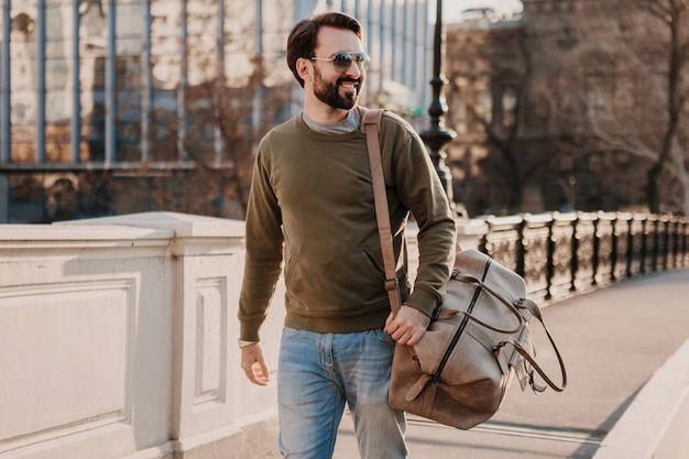 Handsome stylish hipster man walking in city street with leather bag wearing sweatshot and sunglasses, urban style trend, sunny day, smiling happy traveler