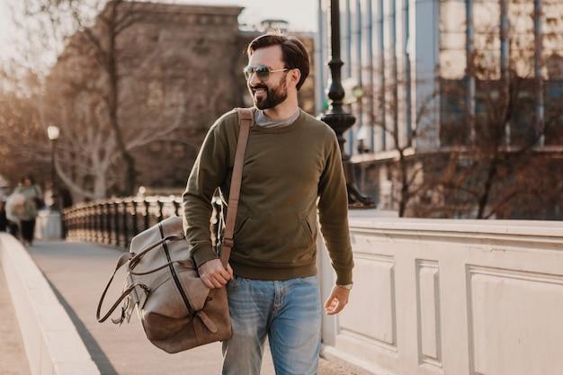 스웨트 샷과 선글라스를 착용하는 가죽 가방, 도시 스타일 트렌드, 화창한 날, 웃는 행복한 여행자와 함께 도시 거리에서 걷는 잘 생긴 세련된 힙 스터 남자