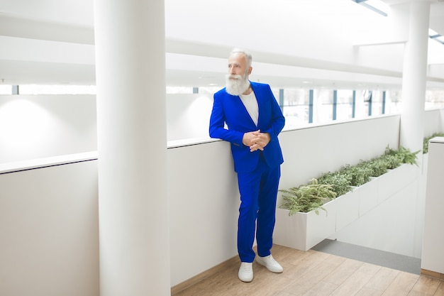 Handsome stylish man on business centre. businessman standing on neutral office background, mature confident man in blue suit.