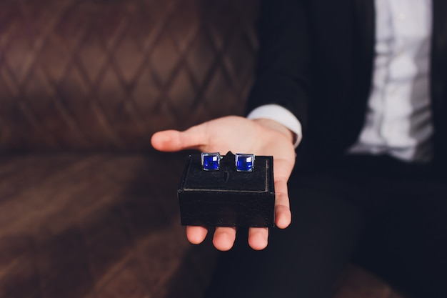 Handsome stylish man in elegant black suit holding cufflinks in a box