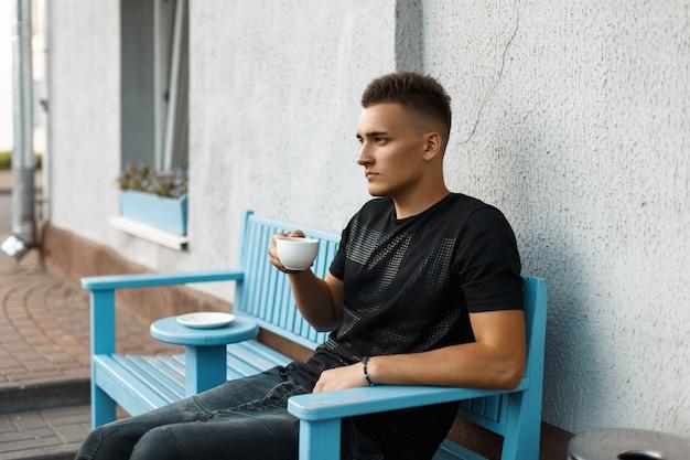 ベンチに座ってコーヒーを飲む黒いシャツを着たハンサムなスタイリッシュな男