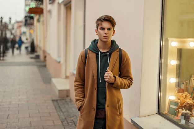 거리에 트렌디 한 까마귀와 트렌디 한 코트에 잘 생긴 세련된 남자