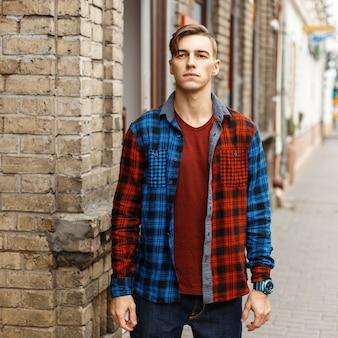 ヴィンテージのレンガの壁の近くのファッショナブルなチェックシャツのハンサムなスタイリッシュな男