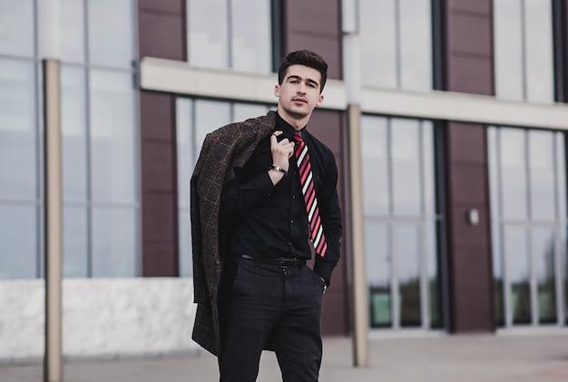 Красивый стильный мужчина в строгой одежде держит в руках пальто